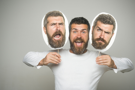 Man with long beard and mustache. Feeling and emotions. Guy or bearded man on grey background. Barber fashion and beauty. Hipster with sad and happy face hold portrait nameplate.