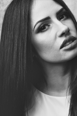 pretty woman face or cute girl portrait with long brunette hair has sexy lips and fashionable makeup on beautiful eyes Stock Photo