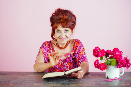 Old woman reading book with glasses at flowers. Writer and poet, granny read fairytale. Teacher or professor, education, teachers day. happy old lady or grandmother. Pension and retirement, old age. Stock Photo