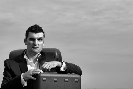 黒いフォーマルジャケットと白いシャツに真剣な顔をしたハンサムな男性ビジネスマンは、曇った空の背景に屋外の革のオフィスアームチェアにブ