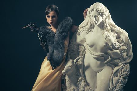レトロな髪、メイクやタバコホルダーを持つ女性。黒の背景にかわいいファッションモデルをピン。黄色いドレスを着た女の子は、彫像で mouthpeice  写真素材