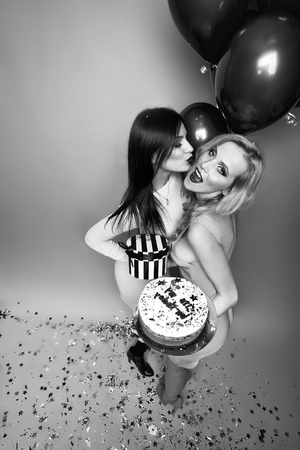 Two pretty sexy young kissing blonde and brunette women holding birthday cake with candles near bunch of red balloons with confetti and present box in studio on yellow backdrop, vertical photo