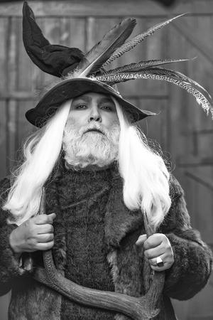 暗い背景に手に鹿の角を持つ鳥の羽と毛皮のコートを持つハンター帽子に長い灰色の髪のひげを持つドルイド老人