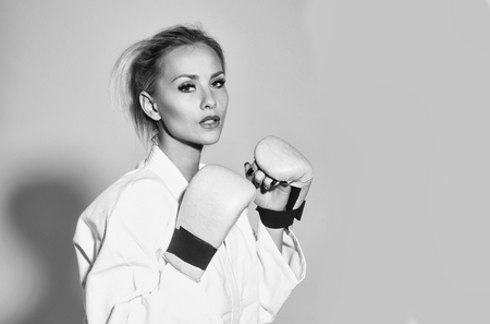 Pretty girl or sexy woman, boxer, fighter, athlete wearing boxing gloves and sexi white shirt with blond, hair on grey background, copy space. Extreme sports and struggle