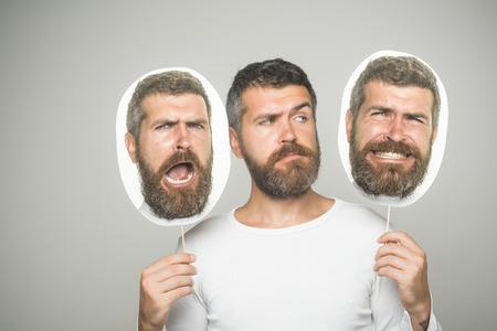 Feeling and emotions. Man with long beard and mustache. Barber fashion and beauty. Guy or bearded man on grey background. Hipster with sad face hold portrait nameplate.