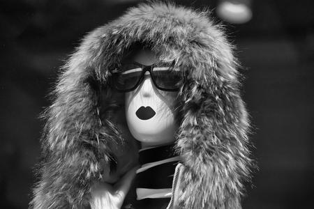 Manier vrouwelijke ledenpop in betoverende zonnebril en bontkap in winkel op bruine achtergrond