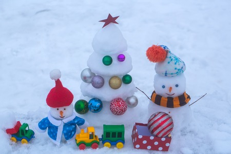 smiley face car: Christmas tree with balls, present box, toy train and car. xmas and new year. Winter holidays concept. Snow sculptures on snowy background. Snowmen with smiley faces in clothing. Stock Photo