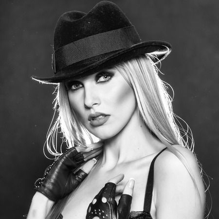 One attractive sexual sensual young blonde woman with long hair in red cowboy hat gloves and bra as strip dancer on black background, square picture
