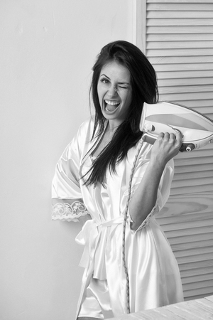 Happy pretty girl or beautiful woman, housewife, with long brunette hair in sexy dressing gown smiling with electric iron in hand indoors on white wall background. Housework and housekeeping