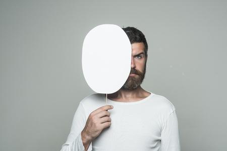 man met lange baard op ernstig gezicht met papieren naamplaatje op grijze achtergrond, kopie ruimte