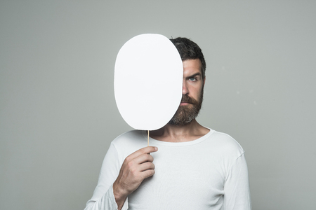 man with long beard on serious face with paper nameplate on grey background, copy space Imagens