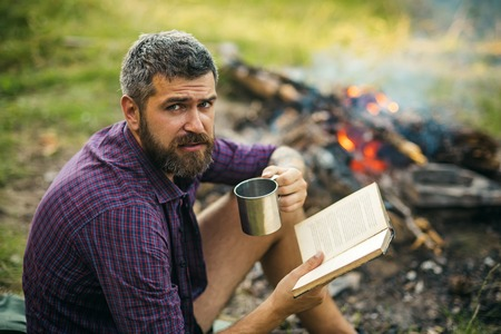 Hipster hiker with book and mug at bonfire on nature. Man traveler read and drink at campfire flame. Camping, hiking, lifestyle. Sustainable education, environment concept. Summer vacation, activity.