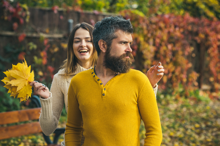 Nature season and fall holiday. Autumn happy couple of girl and man outdoor. Love relationship and romance. Couple in love in autumn park. Man and woman at red tree leaves. Stock Photo