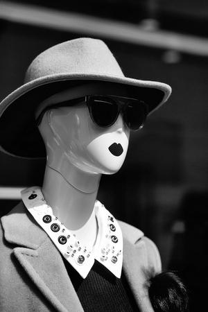 Manier vrouwelijke ledenpop in betoverende zonnebril en kostuum met hoed in winkel op bruine achtergrond