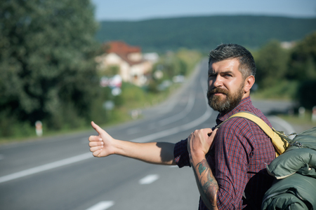 Hipster hiker show thumbs up hand gesture on sunny day. Man with backpack hitchhiking on road. Summer vacation concept. Adventure, discovery, wanderlust. Tourist traveler travel auto stop.