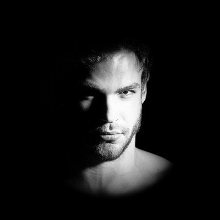 Portrait de vue agrandi d'un bel homme jeune macho barbu avec regard fort yeux noisette et lèvres sexy debout dans la lumière avec impatience en studio sur fond noir, photo carré Banque d'images - 89625518