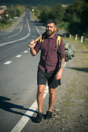 Hipster man with axe and tourist backpack stand on road side on sunny day. Summer vacation, active lifestyle and traveling concept Stock Photo