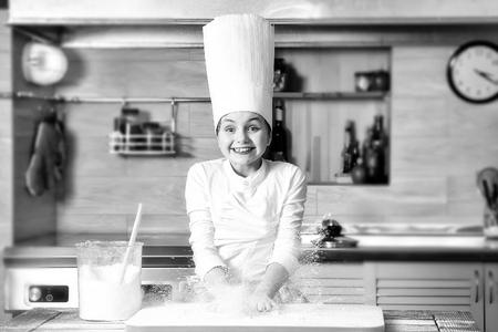 Kochen, Essen, Lernen. Kleines Mädchen, das mit Mehl im Chefhut kocht. Standard-Bild - 91452616