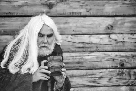 木材の背景に屋外の手で木製のマグカップで深刻な顔に長い灰色の髪とひげを持つドルイドの老人 写真素材