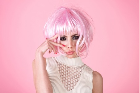 Woman wear pink wig hair on rosy background. Girl with smokey eyes, makeup face. Fashion, style, visage. Hairdressing, beauty salon. Fake, false concept.