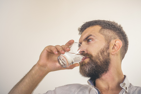 Hangover and thirst. Health and dieting. Man with long beard hold water glass isolated on white background. Life source and healthcare. Hipster drink clean healthy water, refreshing. Imagens