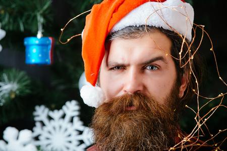 New year holiday and preparation. Santa claus man at christmas tree with garland. party and celebration. Winter holiday and xmas. Christmas man with beard on face