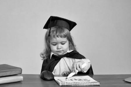 Little boy cute kid student blond in blue shirt black graduation gown and squared cap at school wooden desk drawing in note book by marker near computer mouse and diaries on gray background Stock Photo