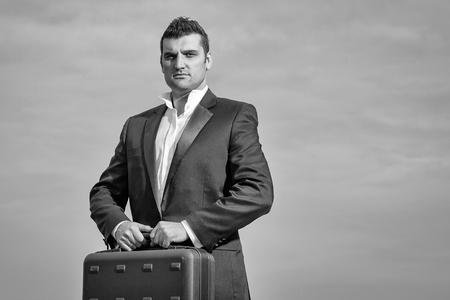 黒いフォーマルジャケットと白いシャツに真剣な顔をしたハンサムな男性ビジネスマンで、曇った空の背景に革張りのオフィスアームチェアにブリ