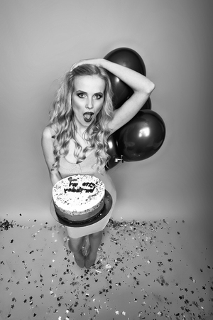 One beautiful emotional young happy blonde woman with long curly hair holding birthday cake with candles near bunch of red balloons with confetti indoor in studio on yellow backdrop, vertical picture