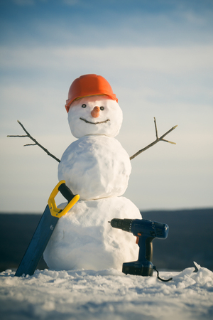 Building and repair work. Happy holiday and celebration. Christmas or xmas decoration. Snowman builder in winter in helmet. New year snowman from snow with saw and screwdriver.