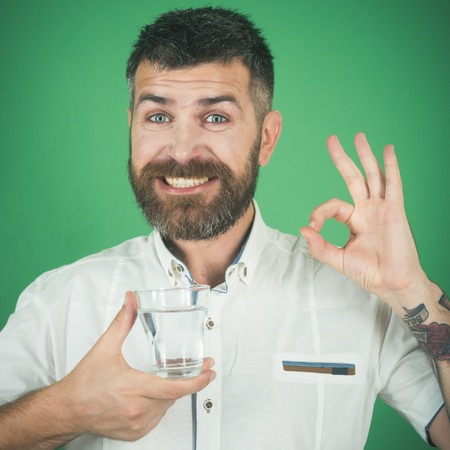 Happy hipster drink clean healthy water with ok gesture, refreshing. Man with long beard hold water glass on green background. Life source and healthcare. Hangover and thirst. Health and dieting.