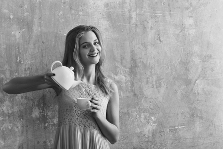 Pretty smiling girl or cute woman with long blond hair and adorable happy face in yellow dress holds tea, coffee cup and teapot on textured wall background, copy space