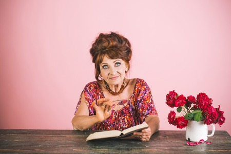 Writer and poet, granny read fairytale. happy old lady or grandmother. Teacher or professor, education, teachers day. Old woman reading book with glasses at flowers. Pension and retirement, old age.