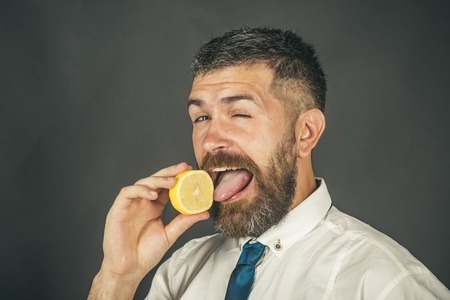 man with long beard lick lemon fruit on black background, healthy food and vitamin, copy space