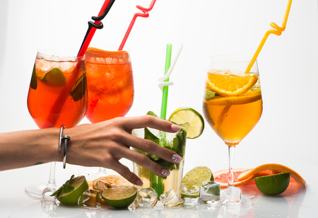 Alcoholic beverage and fruit at restaurant with hand of woman. Fruit slice and cocktail glass at bar. Party and summer vacation. Cocktails isolated on white background with mojito. Drink and food.