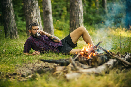 Man traveler drink tea at campfire flame. Camping, hiking, lifestyle. Travel, traveling, wanderlust. Hipster hiker with mug relax at bonfire in forest. Summer vacation concept. Stock Photo