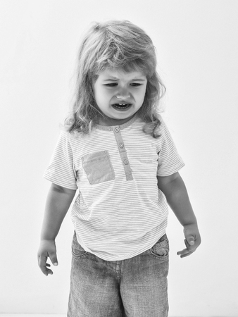 Cute baby boy child with curly blond hair in striped shirt and jeans cries isolated on white background Stock Photo