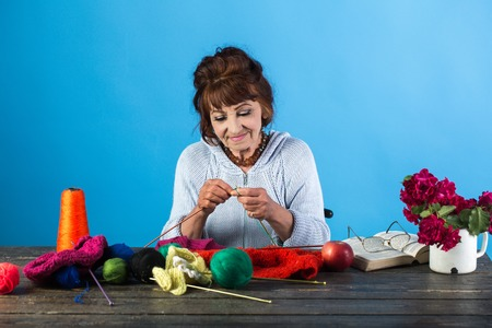 Old woman knitting socks from colorful thread. Old lady or grandmother with needle and yarn. Needlework, knitting hobby. Pension and retirement, old age. Granny character at Christmas eve, womens day. Stock Photo