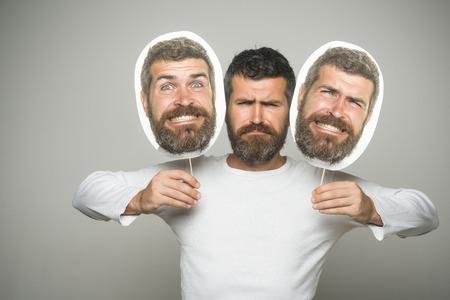感情と感情長いあごひげと口ひげを持つ男。深刻な、幸せで怖い顔を持つヒップスターは、肖像画のネームプレートを保持します。灰色の背景に男