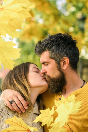 Nature season and fall holiday. Autumn happy couple of girl and man outdoor. Man and woman at yellow tree leaves. Love relationship and romance. Couple in love in autumn park.