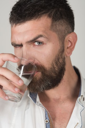 Life source and healthcare. Hangover and thirst. Man with long beard hold water glass on grey background. Hipster drink clean healthy water, refreshing. Health and dieting.