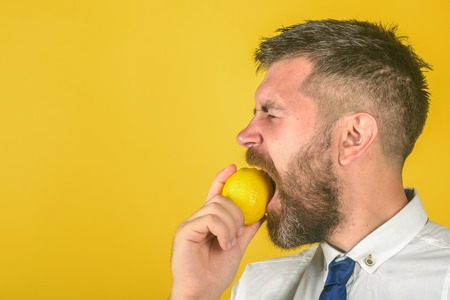 Dieting and fitness. Man with long beard eat lemon. Vitamin citrus at hipster on yellow background. Fruit and healthy organic food. Vegetarian, health and wellbeing, copy space