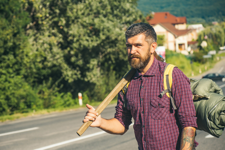 Man hiker with beard hold axe and backpack on road on sunny day. Summer vacation, active lifestyle. Hiking, hitchhiking, auto stop traveling concept Stock Photo