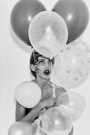 Pretty surprised girl or sexy woman with cute curly lock of blond hair, fashion hairstyle, and rosy lips, stylish makeup, on young face with party balloons, colorful, pink, hearts on white background