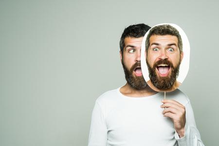 Man met lange baard en snor. Hipster met verrast gezicht houdt portret naamplaatje. Man of bebaarde man op grijze achtergrond. Gevoel en emoties. Kapper mode en schoonheid., Kopie ruimte