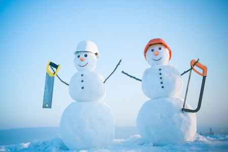 Christmas or xmas decoration. Happy holiday and celebration. New year snowman from snow with saw. Building and repair work. Snowman builder in winter in helmet.