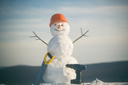 Happy holiday and celebration. Snowman builder in winter in helmet. New year snowman from snow with saw and screwdriver. Christmas or xmas decoration. Building and repair work.
