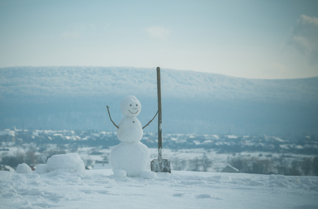 New year snowman from snow with shovel. Christmas or xmas decoration. Snowman builder in winter. Happy holiday and celebration. Building and repair work. Stock Photo