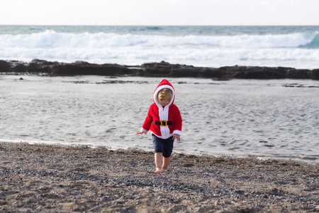 Cute baby boy in red santa coat with hood and shorts walks barefoot on grey pebble beach by sea on sunny summer day on natural background Stock Photo