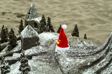 Beautiful sandcastle or sculpture, miniature building with red santa hat on grey sandy beach surface outdoors on sand texture background